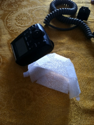 Meikie MK-300 flash beside DiY flash diffuser made of plastic foam sheeting and Scotch tape.